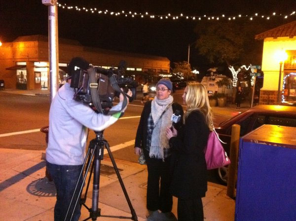 San Diego Cash Mob organizer Lauren Way with one of the TV news crews covering the event.