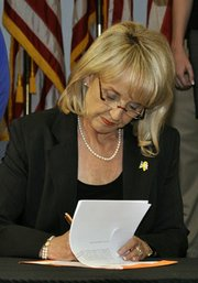Arizona Gov. Jan Brewer signs the SB 1070 immigration legislation into law in April 2010. 