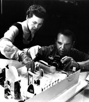 "Ray and Charles Eames photographing an early model of the exhibition ""Mathematica: A World of Numbers … and Beyond,"" 1960."