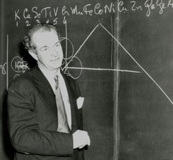 Professor Linus Pauling stands in front of a chalkboard. Pauling had a brilliant 40-year career at California Institute of Technology making revolutionary discoveries in chemistry, physics, molecular biology and medicine.