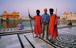 Michael Palin with two guardians of the temple, Amritsar, India. Their robes and spears symbolise the dual nature of the Sikhs: service and defence. In the background the Harimandir (Hari is God, Mandir is temple) has 1100lb (500 kg) of gold on its walls.