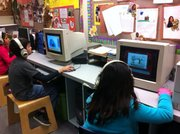 Elementary school children practice their English skills with an interactive program mean for English Language Learners.