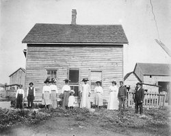 Historical photo of a free Black family in front of home.