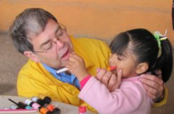 Bill Phelps plays with a girl at the Casa Hogar Sion orphanage in TIjuana.