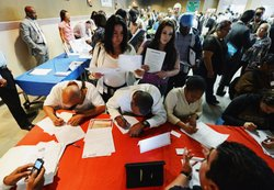 Job seekers pick up job applications at Fresco Community Market during Los Angeles Mission's 11th annual Skid Row Career Fair on May 31, 2012 in Los Angeles, California.