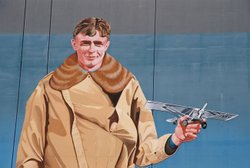 """Lucky/Spirit"" was painted by John Whalen in 1997. It features aviator Charles Lindbergh and his monoplane, The Spirit of St. Louis."