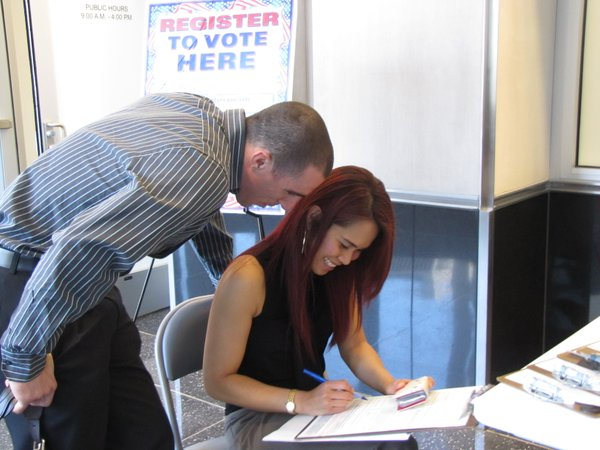 A new American citizen registers to vote with some help from a friend after a May naturalization ceremony in Las Vegas.