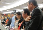 New citizens recite the Pledge of Allegiance during a June naturalization ceremony in North Las Vegas.