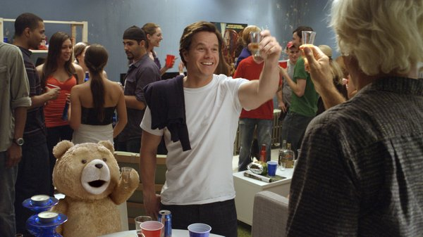 "Ted (voiced by Seth MacFarlane) and John (Mark Wahlberg) drink shots with Sam J. Jones in ""Ted."""