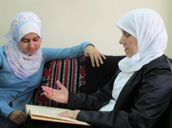 Houda al-Habash talking with her daughter, Enas, about how she started work as a preacher.