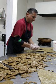 Luis Flores, owner of Las Cruces Candy Company, prepares pecan brittle using green chile powder from peppers grown in New Mexico.