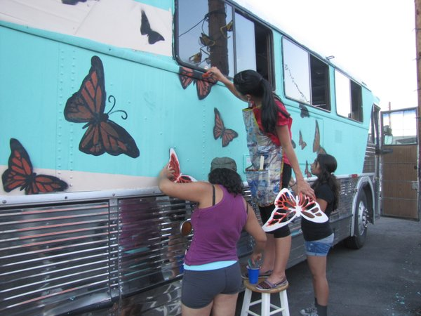 Activists paint the vintage bus they plan to drive across the South to protest deportations.