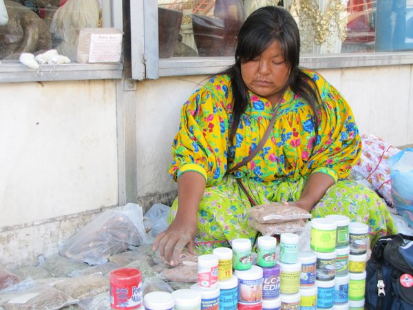 An indigenous Tarahumara woman sells herbal medicines from a sidewalk in the downtown marketplace of Ciudad Juarez.