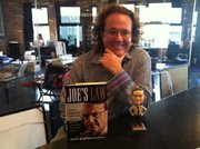 Jason Rose, cofounder of Rose+Moser+Allyn Public & Online Relations, with a Joe Arpaio bobblehead and a copy of his memoir.