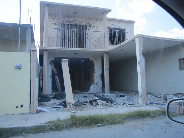 This house in Nuevo Laredo, Mexico once housed kidnap victims. The federal police raided the house and left it peppered with bullet holes.