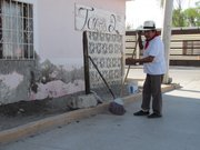 Abraham Hernndez cleans up outside his house in La Nueva Era neighborhood of Nuevo Laredo. Before streets were paved here, he had to deal daily with dust and heavy mud when it rained.