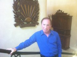 Bob Shillman, founder of Cognex Corp., stands next to his family crest in his Rancho Santa Fe home.
