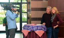 "Alex Trebek poses for an interview with a member from Aviano Air Base, Italy, Oct. 9, 2012. Trebek autographed and posed for pictures with Airman and their spouses while searching for ""Jeopardy"" contestants to participate in a military edition of the game show."