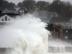 Waves crash over a road as Hurricane Sandy comes up the coast Monday in Winthrop, Mass. Economists are predicting the storm will cost tens of billions of dollars.