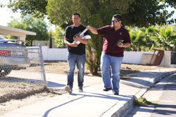 David Ramirez, left, and Eric Garza of The Libre Initiatve, a conservative national group, leave flyers at a Latino-heavy neighborhood in Las Vegas.