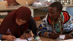 Rafea in the classroom at Barefoot College with a fellow student looking at what she's writing.