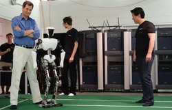 David stands next to CHARLI, a robot built by Dennis Hong (far right) and his students at RoMeLa Lab at Virginia Tech.