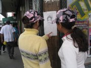 Two girls read a missing person flier posted downtown Juárez.