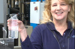Marsi Steirer with the San Diego Public Utilities Department holds a flask of recycled wasterwater that she says is cleaner than what comes out of your tap. 