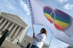 Same-sex marriage proponent Kat McGuckin of Oaklyn, New Jersey, holds a gay marriage pride flag while standing in front of the Supreme Court November 30, 2012 in Washington, DC.