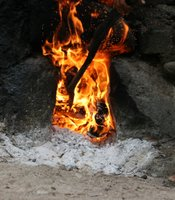 A mezcalero, or mezcal producer, stands beside a fire that heats the still where the mezcal is made.