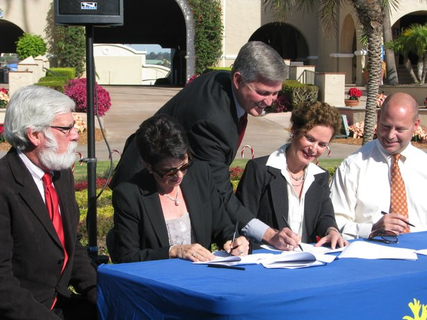 Don Moser, former Mayor of Del Mar, Lee Haydu, Deputy Mayor of Del Mar, Dave Roberts, Deputy Mayor of Solana Beach, Lisa Heebner of Solana Beach and Adam Day, President  of the 22nd District Agricultural Association, sign an agreement to end a lawsuit over the Master Plan for the Del Mar Fairgrounds