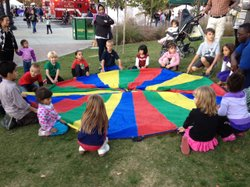 Children circle around the colorful parachute at the City of El Cajon's birthday event.