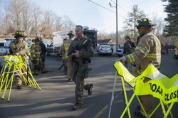 Connecticut State Police walk near the scene of an elementary school shooting on December 14, 2012 in Newtown, Connecticut.