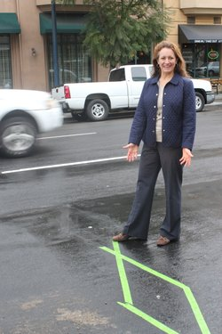 SDSU Professor Sherry Ryan poses over an electronic loop, embedded in the street, that keeps track of the number of bikes which travel on that route.
