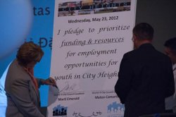 City Council District 9 candidates Marti Emerald and Mateo Camarillo sign a pledge promising to bring more youth jobs to City Heights.