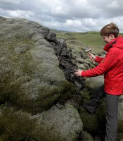 Anja Schmidt uses a rock hammer to retrieve a lava sample