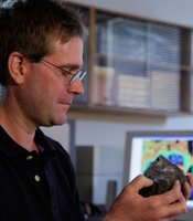 Chris Hayward inspects a volcanic rock sample at his desk.