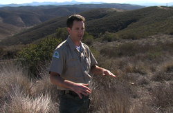Matt Sanford, senior ranger of Mission Trails Park, stands in front of a piece of open space that will make San Diego's biggest park even bigger.