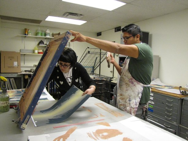 Tom Greyeyes works on a print at Arizona State University on Jan. 8 with the assistance of student, Emily Lewis.