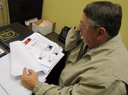 Investigator Terry Mulligan with the 9th Judicial District of New Mexico reviews files in a case involving driver's license fraud.