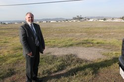 Peter Drinkwater, the director of airports for San Diego County, stands by the 70 blank acres that will be redeveloped to expand Gillespie Field.