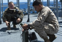 Setting up a portable communication array on board a ship.