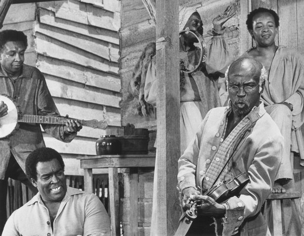 "Louis Gossett Jr. (as Fiddler) plays the fiddle in the 1977 miniseries ""Roots."""