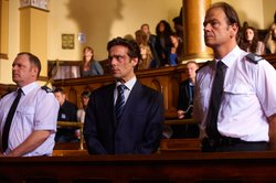 John Light as Mark Keane (center) in court.