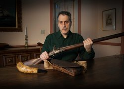 Don Troiani, a historical artist known for his paintings of soldiers and battles, cradles a vintage musket.
