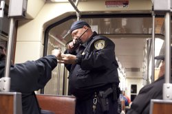 Trolley cop Jeff Metz asks a passenger for her ticket.