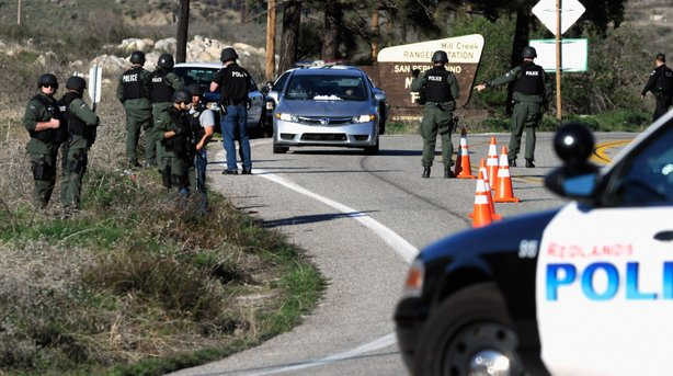 Police search cars at a blockade as they come down the mountain during a manhunt for the former Los Angeles Police Department officer who is suspected of triple murder on February 12, 2013 in Yucaipa, California.