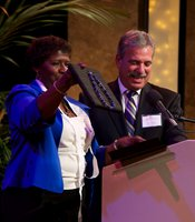 PBS NewsHour host Gwen Ifill shows the crowd the necklace KPBS General Manager Tom Karlo presents to her on behalf of KPBS Producers Club at the Shiley Studio on 2/9/13.