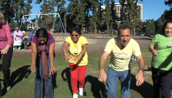 Michael Coleman, the director of Laughter Matters, and other laughter yoga participants play in Balboa Park.
