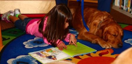 Olivia Figueroa, a 7-year-old with the Exceptional Family Member Program, reads a book to Muddy, a Labrador Retriever with Independent Therapy Dogs, Inc., at the Library aboard MCAS Miramar on Feb. 13.